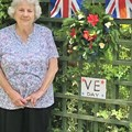 Here is Pam Smith from Fleet Morning Guild, showing the display she made outside her house for V E Day. It was much admired by passers by!